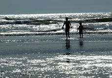 Two Kids Playing on the Beach as the Sun is Glistening on the Wa Stock Photos