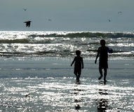 Two Kids Playing on the Beach as the Sun is Glistening on the Wa Royalty Free Stock Photo