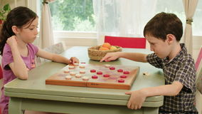 Two kids playing checkers. Tracking shot of Two kids playing checkers stock video footage