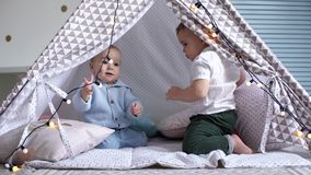 Two kids playing with a garland in a child`s tent. One crawls away from another. Two kids playing with a garland in a children`s tent. One boy crawls away from stock video footage