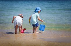 A boy and a girl playing with beach toys on the beach. stock photo