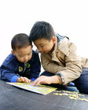 Two kids playing jigsaw. A candid picture of two chinese boys playing jigsaw attentively Stock Photos