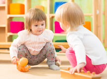Two kids playing in kindergarten room Royalty Free Stock Images
