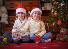 Two kids playing with lanterns under Christmas tree Royalty Free Stock Photos