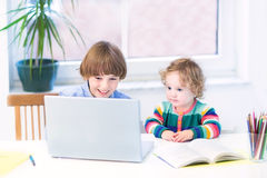 Two kids playing with laptop sitting at white desk Royalty Free Stock Image