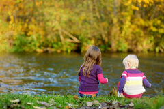 Two kids playing by a river. On autumn day Stock Image