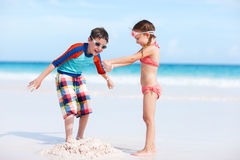 Two kids playing with sand Stock Images