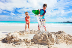 Two kids playing with sand Stock Photos