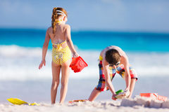 Two kids playing with sand. Brother and sister playing with sand at tropical beach Stock Images