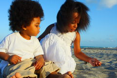 Two kids playing in the sand. Two young children playing in the sand Stock Images