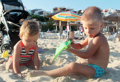 Two kids playing with sand. On the beach Royalty Free Stock Photo