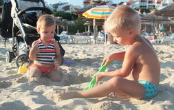 Two kids playing with sand. On the beach Stock Images