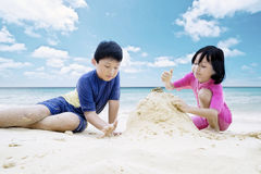Two kids playing sand on beach Royalty Free Stock Photography