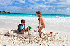 Two kids playing with sand. Brother and sister playing with sand at tropical beach Royalty Free Stock Photo