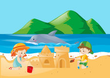 Two kids playing sandcastle on the beach Royalty Free Stock Image