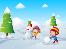 Two kids playing snow ball in the snow field Royalty Free Stock Photography
