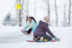 Two kids playing on a snow sled in winter stock images