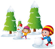Two kids playing snowman in the snow field Stock Images