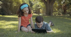 Two kids playing with a tablet computer stock video footage