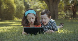 Two kids playing with a tablet computer stock video