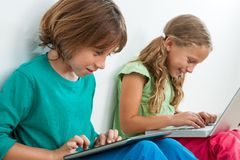 Two kids playing on tablet and laptop. Stock Images