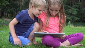 Two kids playing with tablet outdoors stock footage