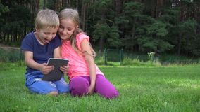 Two kids playing with tablet outdoors stock video footage