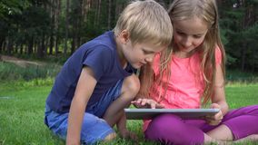 Two kids playing with tablet outdoors stock video