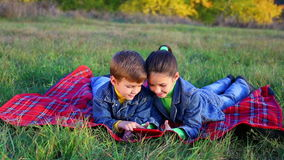 Two kids playing with tablet PC. Two happy kids playing with tablet pc on the autumn lawn, outdoor shooting stock video footage