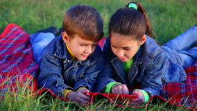 Two kids playing with tablet PC. Two smiling kids playing with tablet pc on the autumn lawn, outdoor shooting stock video