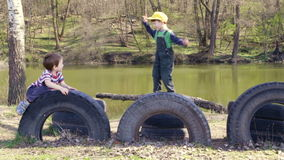 Two kids playing together jumping and climbing on old tires. In the park near river, spring day stock video