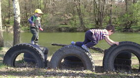 Two kids playing together, jumping and climbing on tires. Two kids playing together - jumping and climbing on tires in park near river, spring outdoor shooting stock footage