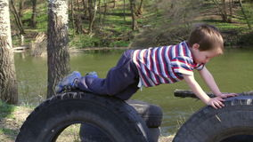 Two kids playing together on tires in playground. Two kids playing together - jumping and climbing on tires in playground near river, spring outdoor shooting stock video footage
