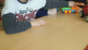 Two kids playing toy model cars at the table stock footage
