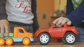 Two kids playing toy model cars at the table stock video footage