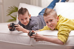 Two kids playing video games. Two little boys having lots of fun with video games Royalty Free Stock Photography