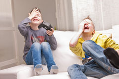 Two kids playing video games. Two little boys having lots of fun with video games Stock Image