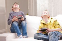 Two kids playing video games Stock Photos