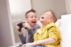 Two kids playing video games. Two little boys having lots of fun with video games Royalty Free Stock Image