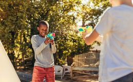 Children enjoys playing with squirt guns outdoors. Two kids playing with water guns in backyard. Children enjoys playing with squirt guns outdoors stock photos