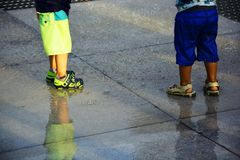 Two kids in are wet and standing on the cement floor stock images