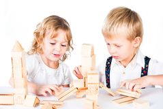 Two kids playing with wooden blocks indoor Stock Photo