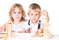 Two kids playing with wooden blocks indoor Stock Images