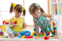 Two kids playing with wooden blocks in their room royalty free stock photography