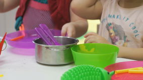Two kids plays with plastic children's tableware stock video footage