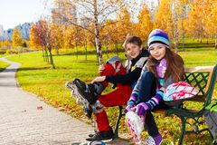 Two kids putting on roller blades Stock Image