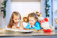 Two kids read a book. Two sisters. Concept New Year, Merry Chris. Tmas, holiday, vacation, winter, childhood royalty free stock photos