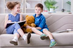 The two kids reading books at home royalty free stock photography