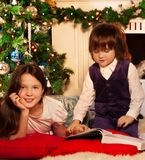 Two kids reading Christmas book Royalty Free Stock Photo