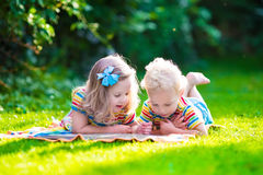 Two kids reading in summer garden. Kids reading a book in summer garden. Children study. Boy and girl play in school yard. Preschool friends playing and learning Royalty Free Stock Photo